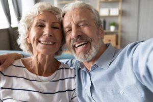 old couple with dental implants who undergo jaw bone grafting