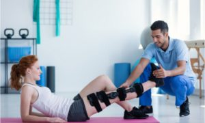 The therapist tries to stretch the athlete's leg.