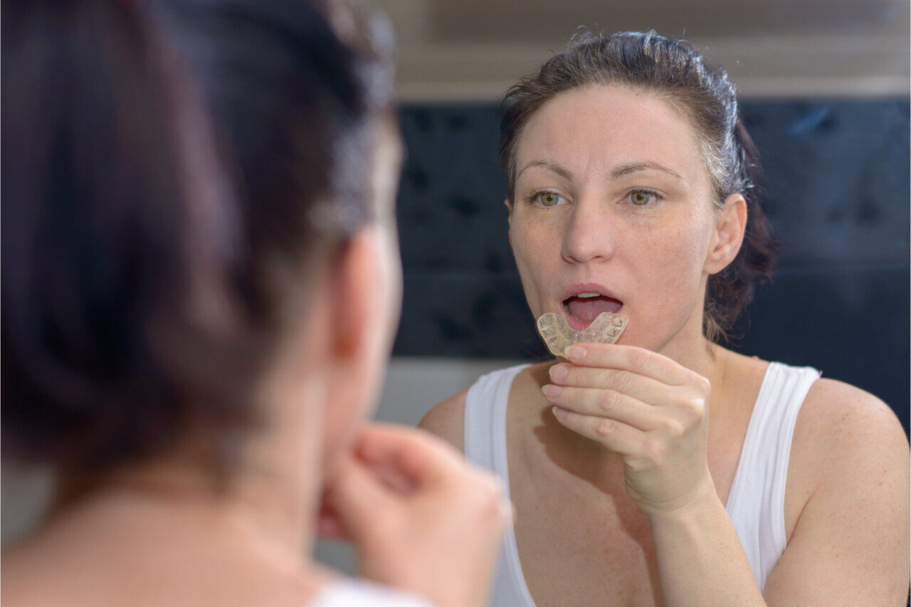 A woman puts her mouth guard for jaw pain before sleeping.