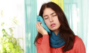The woman uses a cold compress to treat her swollen cheeks.